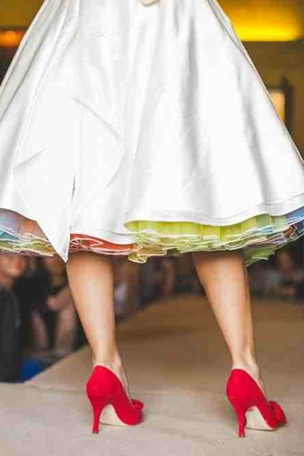 White wedding dress with rainbow petticoat and red shoes